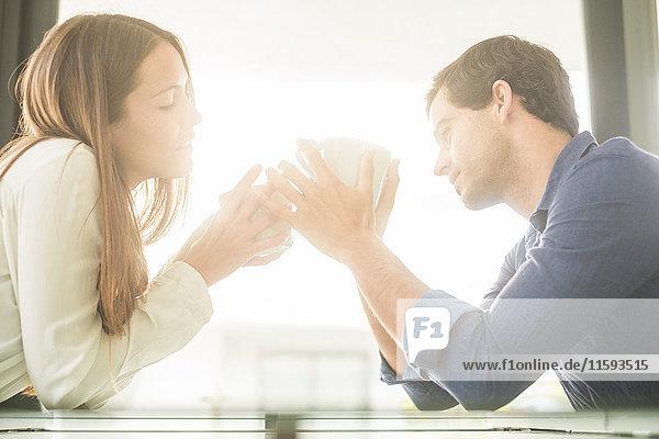 Junges Paar im Gegenlicht am Tisch sitzend mit Tassen Junges Paar im Gegenlicht am Tisch sitzend mit Tassen