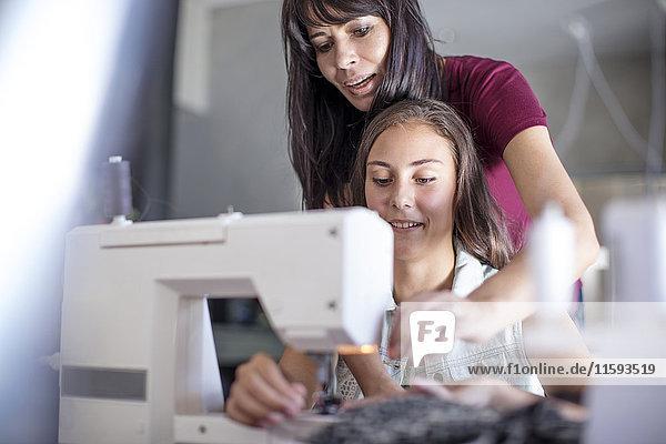 Mutter und Tochter nähen zusammen Mutter und Tochter nähen zusammen