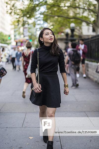 USA  New York City  Manhattan  modische junge Frau in schwarz gekleidet  auf dem Bürgersteig laufend