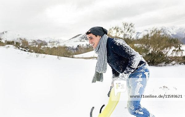 Junger Mann beim Schlittenfahren im Schnee