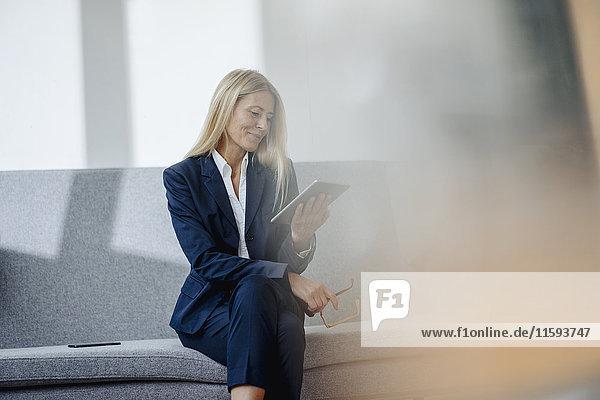 Lächelnde Geschäftsfrau sitzt auf der Couch und hält eine Tablette.