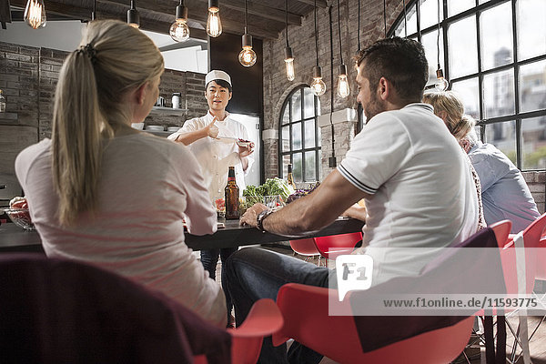 Köchin im Gespräch mit Schülern im Kochkurs