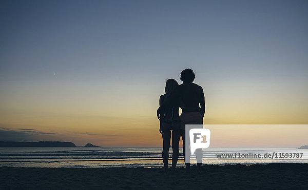 Junges Paar beobachtet den Sonnenuntergang am Strand