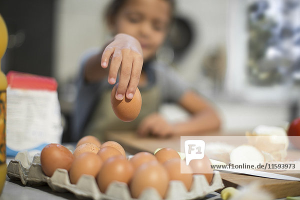 Girl in kitchen taking egg