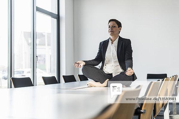 Geschäftsfrau auf dem Konferenztisch sitzend meditierend