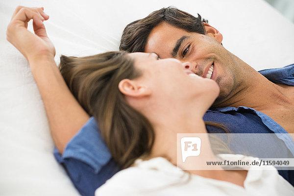 Lächelndes junges verliebtes Paar im Liegen