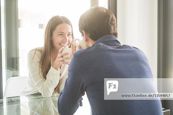 Fröhliches junges Paar am Tisch mit Kaffeetassen