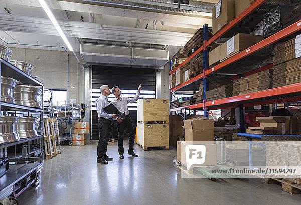 Zwei Geschäftsleute in der Fabrikhalle  die sich unterhalten