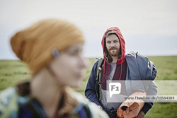 Lächelnder Mann mit Frau im Vordergrund auf einer Reise