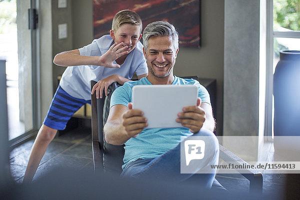 Glücklicher Vater und Sohn mit digitalem Tablett zu Hause