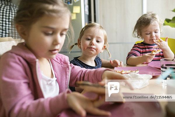 Kleine Mädchen zu Hause beim Pizzaessen