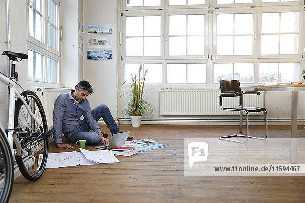 Mann mit Laptop auf dem Boden in einem modernen informellen Büro
