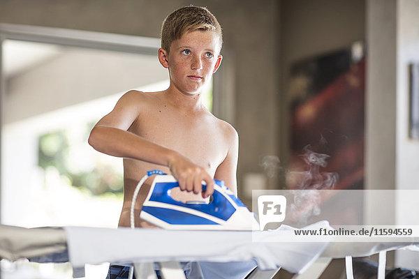 Shirtless Teenager Junge Bügelbekleidung zu Hause