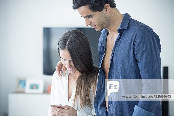 Verliebtes junges Paar schaut zu Hause aufs Handy