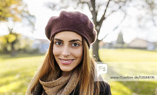 Porträt einer lächelnden jungen Frau mit Baskenmütze im Herbst