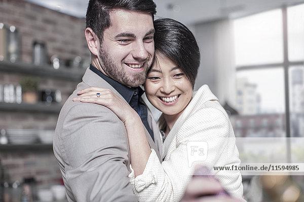 Lächelndes Paar  das sich zu Hause umarmt