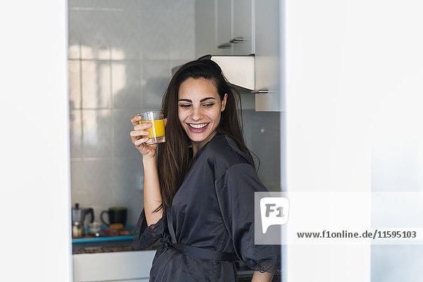 Porträt einer lachenden jungen Frau mit einem Glas Orangensaft in der Küche