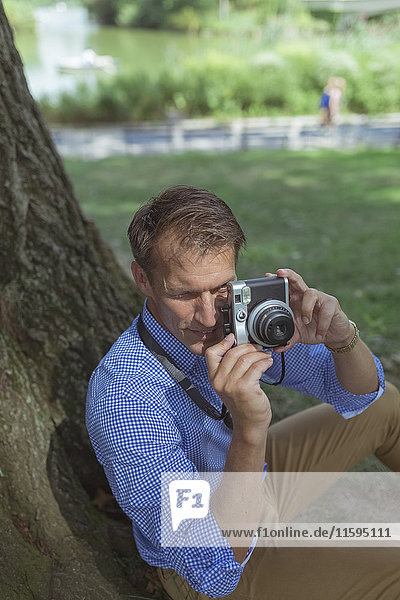 Man taking pictures with camera in a park