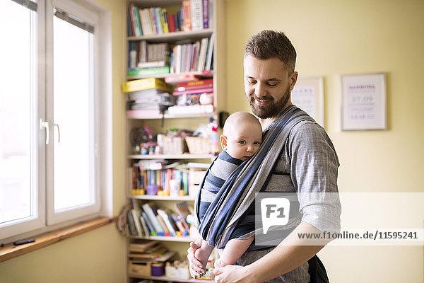 Vater mit Sohn im Tragetuch zu Hause