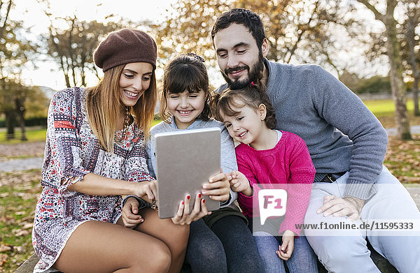Family sitting on bench in autumnal park taking selfie with tablet
