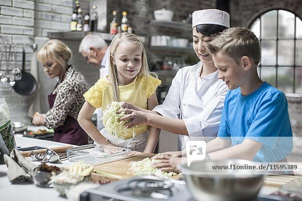 Köchin unterrichtet Kinder im Kochunterricht