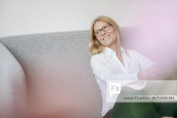 Lächelnde entspannte Geschäftsfrau auf der Couch sitzend