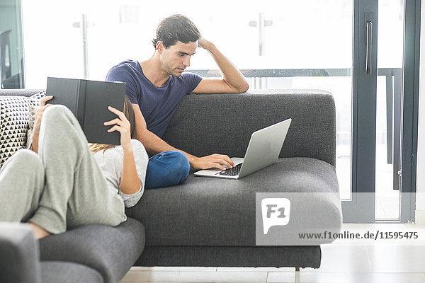 Junges Paar auf der Couch entspannt mit Buch und Laptop