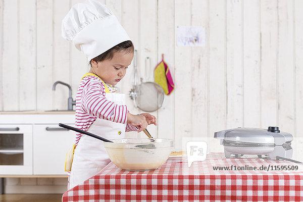 Kleines Mädchen  das Waffeln zubereitet und einen Kochhut trägt.