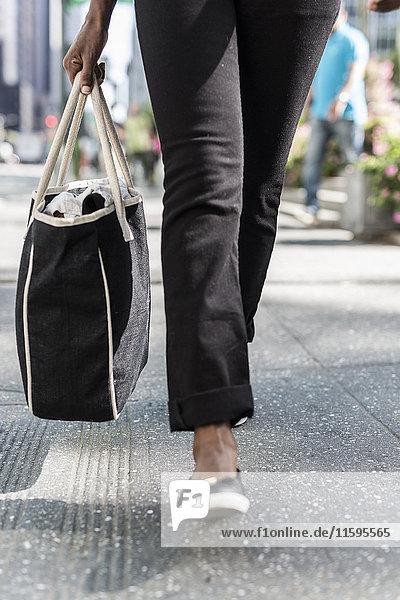 Frau mit Einkaufstasche  Teilansicht