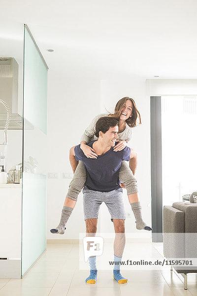 Verspielter junger Mann mit Freundin Huckepack zu Hause