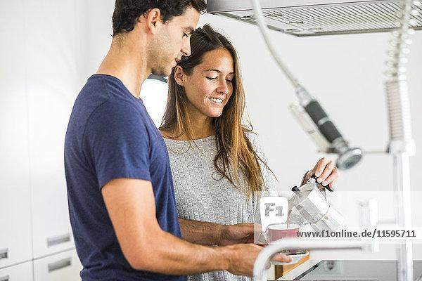 Junges Paar in der Küche gießt Kaffee in die Tasse