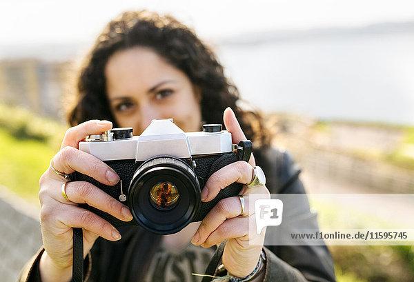 Porträt einer Frau mit einer altmodischen Kamera im Freien