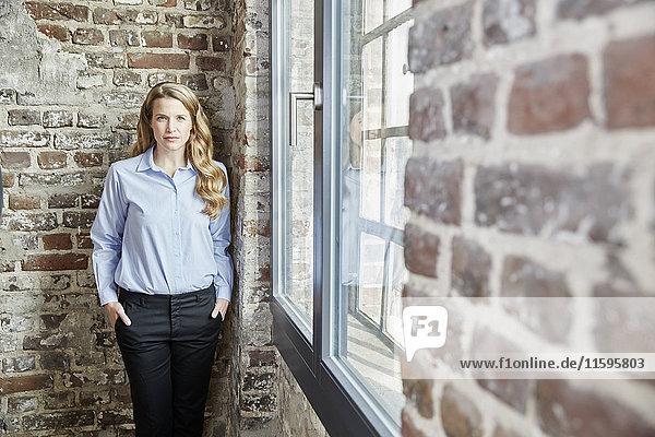 Porträt einer selbstbewussten Geschäftsfrau an der Backsteinmauer