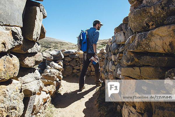 Bolivien  Titicacasee  Isla del Sol  Mann mit Rucksack und Reiseführer  Wanderung durch die Ruinen von Chinkana