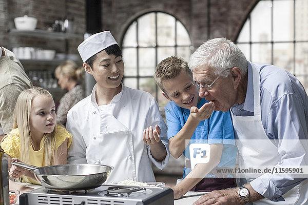Teilnehmer und Köchin im Kochkurs