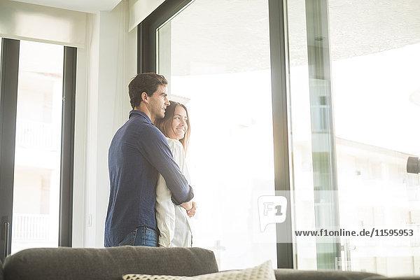 Glückliches junges verliebtes Paar am Fenster Glückliches junges verliebtes Paar am Fenster