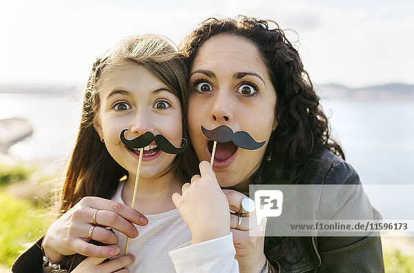 Mother and daughter having fun holding fake moustaches