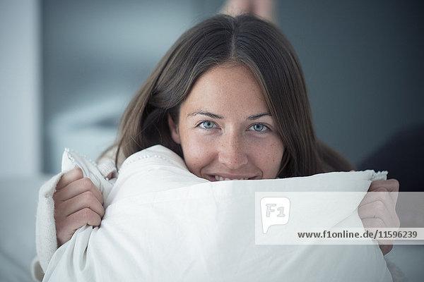 Porträt einer glücklichen jungen Frau auf dem Bett liegend