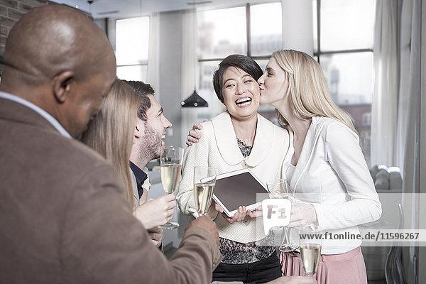 Fröhliche Frau zeigt Freunden mit Champagnergläsern zu Hause eine Tablette.