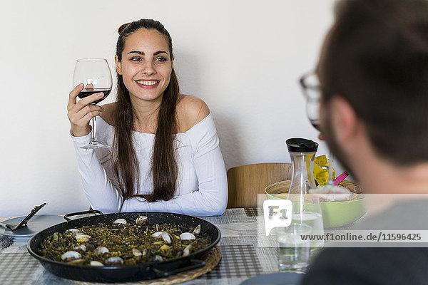 Porträt einer lächelnden Frau mit einem Glas Rotwein am gedeckten Tisch mit Blick auf ihren Freund.
