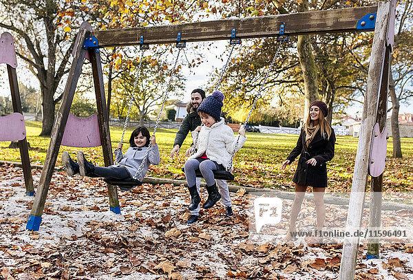 Fröhliche Familie beim Schaukeln im Herbst