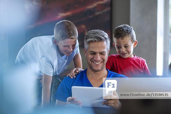 Kinder  die mit ihrem Vater auf einem digitalen Tablett suchen