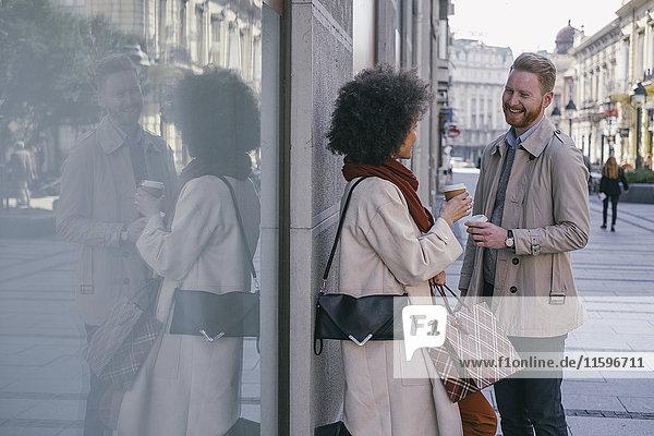 Glückliches Paar in der Stadt mit Kaffee zum Mitnehmen und Einkaufstaschen