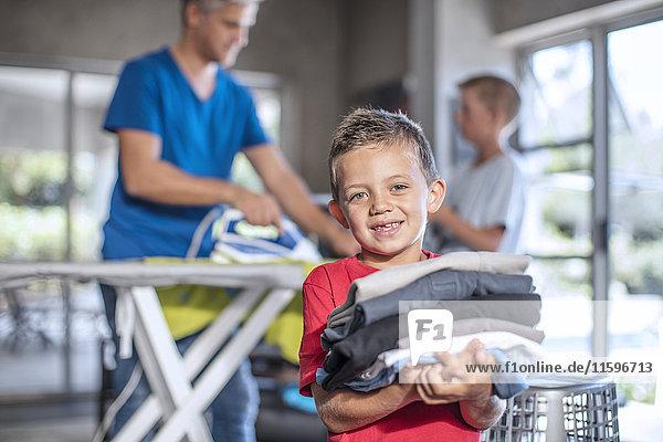 Lächelnder Junge hilft bei der Arbeit mit gefalteten Kleidern