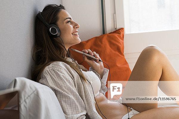 Lächelnde junge Frau sitzt auf dem Bett mit Handy und hört Musik über Kopfhörer.