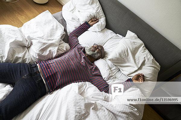 Erwachsener Mann auf dem Bett liegend  lächelnd