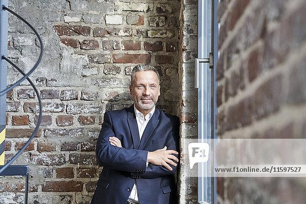 Porträt eines selbstbewussten Geschäftsmannes  der sich an eine Ziegelmauer lehnt