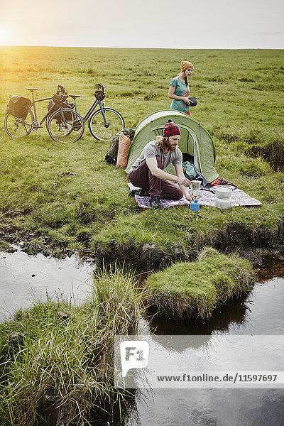 Deutschland  Schleswig-Holstein  Eiderstedt  Paar mit Fahrrädern beim Camping in Sumpflandschaft