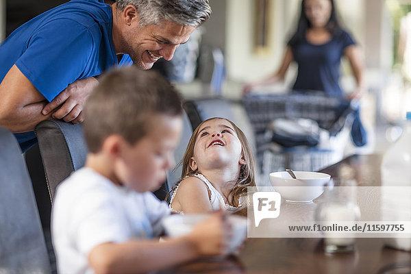 Glückliche Familie beim Frühstück am Tisch