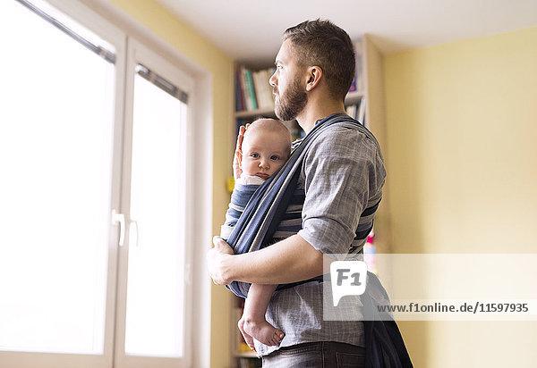 Vater mit Sohn im Tragetuch zu Hause aus dem Fenster schauend